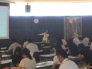 伊達市役所1階の吹き抜けの研修所で、スクリーンに手を指しながら解説する小田順子の写真